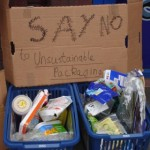 sign with the words 'say no to unsustainable packaging' alongside boxes of packaging