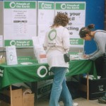 image of the stall with various posters about recycling and members of the public filling in a survey about their recycling service