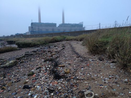 Tilbury power station, with the foreshore strewn with rubbish.