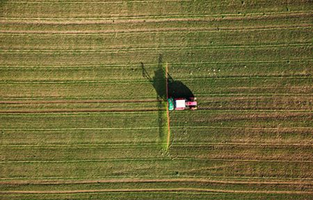Aerial view of tractor spraying a field